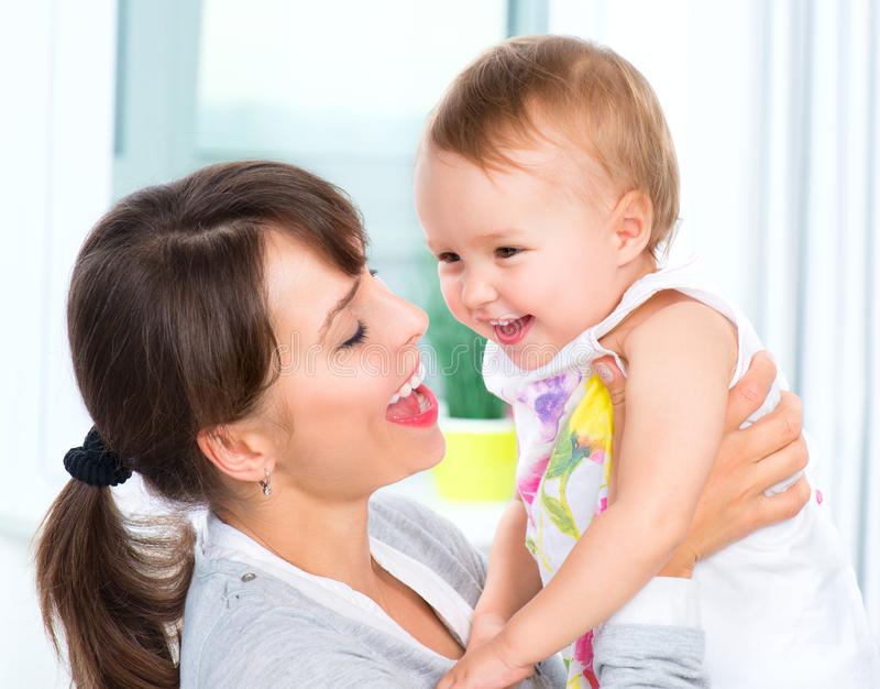 Happy Smiling Mother and Baby. Kissing and hugging at Home stock photos