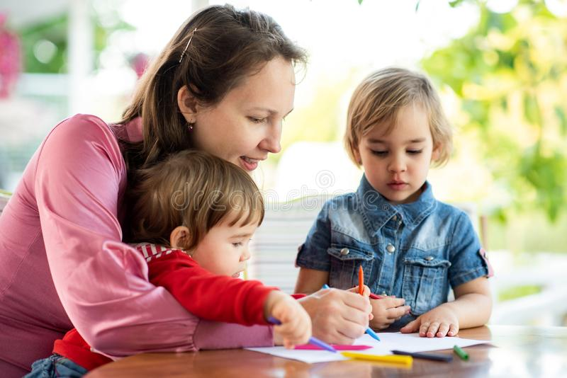 Happy Smiling Mother And Child Daughter Having Fun and Drawing Pictures in Garden in Summer Season stock photography