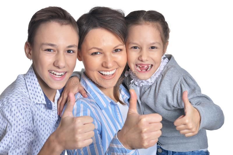 Happy smiling mother and children showing thumbs up together on white background royalty free stock photography