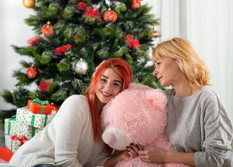 The happy and smiling mother with the daughter sit at a Christmas tree with a big pink teddy bear stock photos
