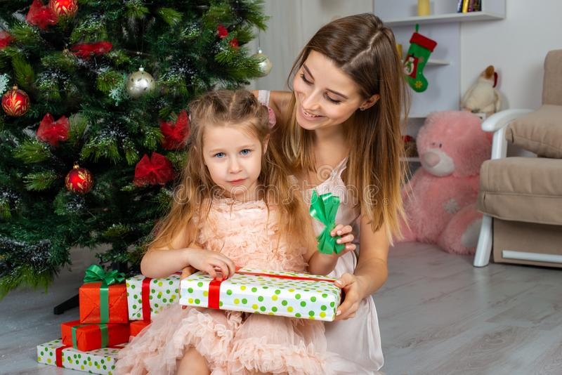 The happy and smiling mother with the daughter sit at a Christmas tree with gifts in hands royalty free stock photo