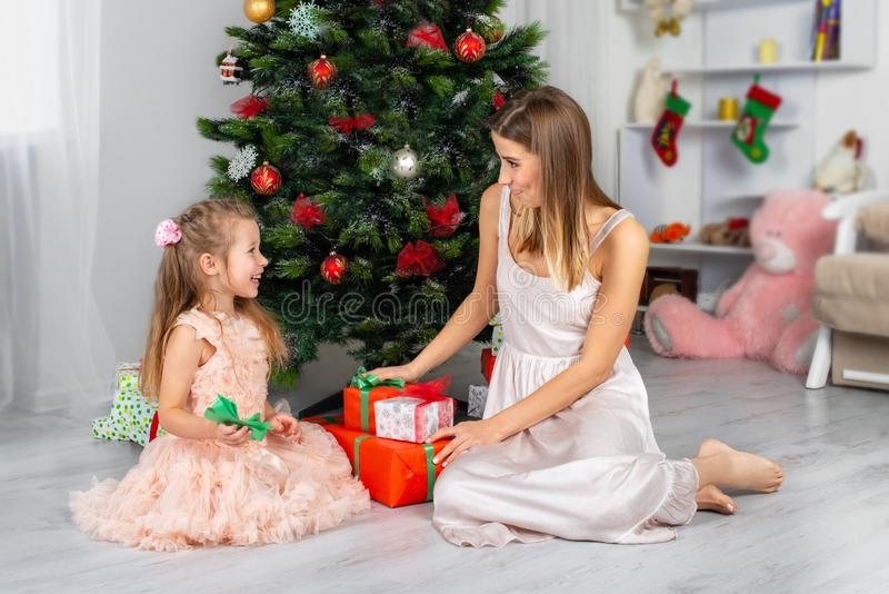 The happy and smiling mother with the daughter sit at a Christmas tree with gifts in hands stock image