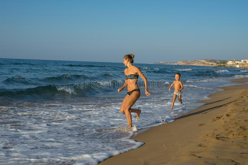 Happy smiling mother and her son playing and running on the beach. Concept of friendly family. Happy summer days. Balos Lagoon stock photos