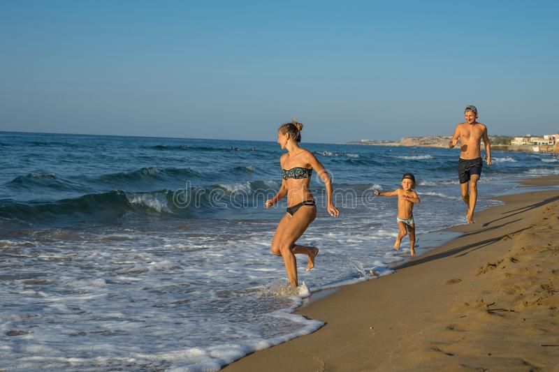 Happy smiling mother and her son playing and running on the beach. Concept of friendly family. Happy summer days. Greece. Balos stock image