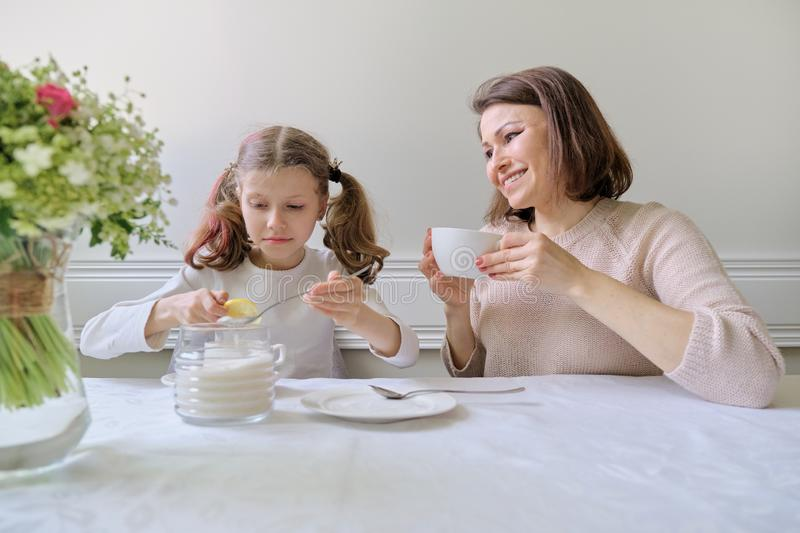 Happy smiling mother and little daughter drinking at table of cups stock images