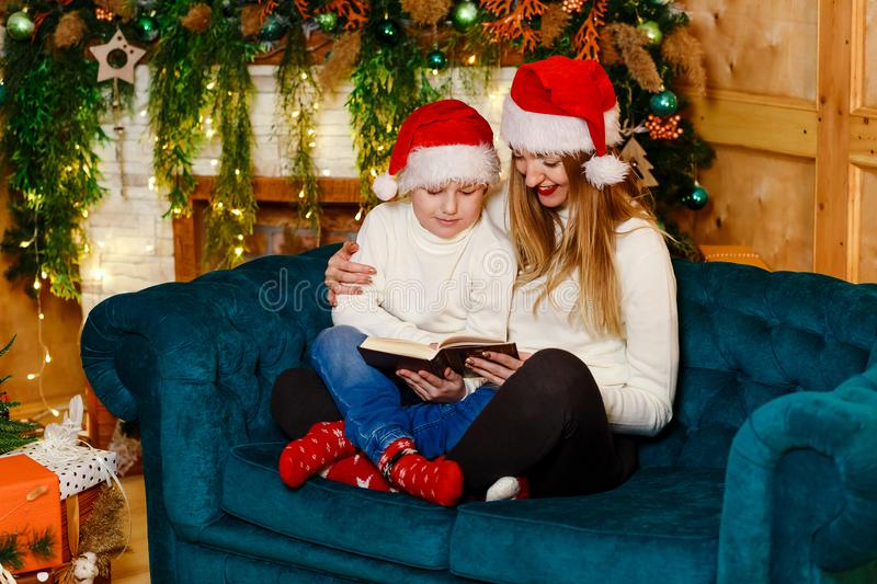 Happy mother and little son in matching sweaters and red caps reading a book sitting on the couch near the fireplace royalty free stock photography