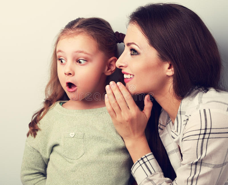 Happy smiling mother whispering the secret to her surprising daughter in ear. Closeup toned portrait royalty free stock photography