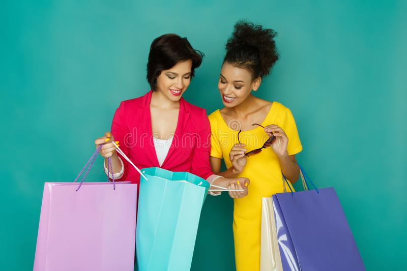 Excited happy multiethnic girls with shopping bags royalty free stock photo