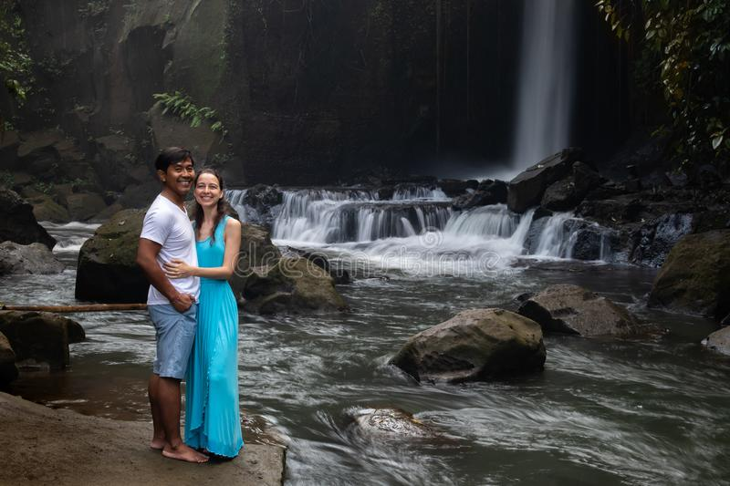 Happy smiling multiracial couple hugging near waterfall in tropical forest. Young mixed race couple on vacation in Asia. Ubud, stock image