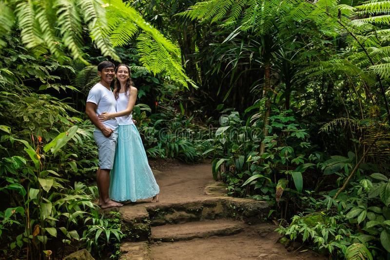 Happy smiling multiracial couple hugging on walking trail in tropical forest. Young mixed race couple on vacation in Asia. Ubud, stock images