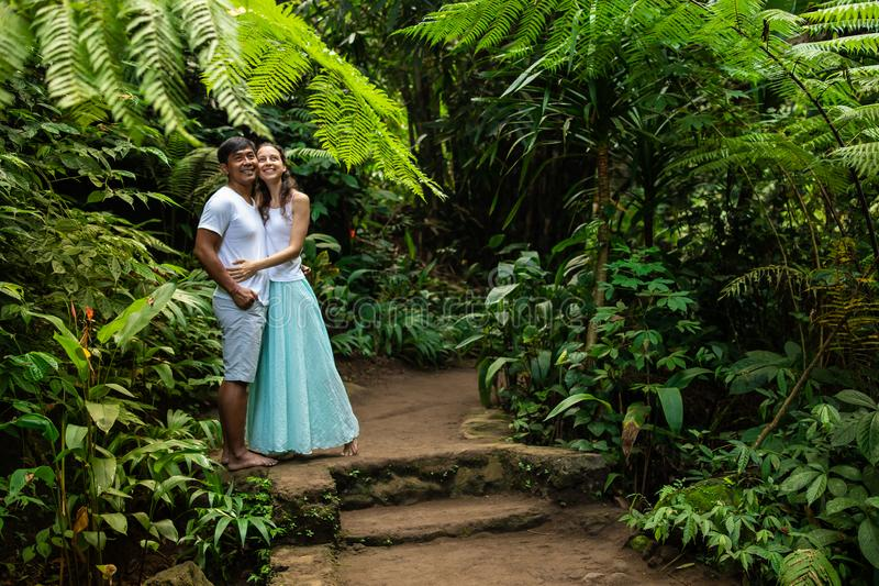 Happy smiling multiracial couple hugging on walking trail in tropical forest. Young mixed race couple on vacation in Asia. Ubud, royalty free stock photography