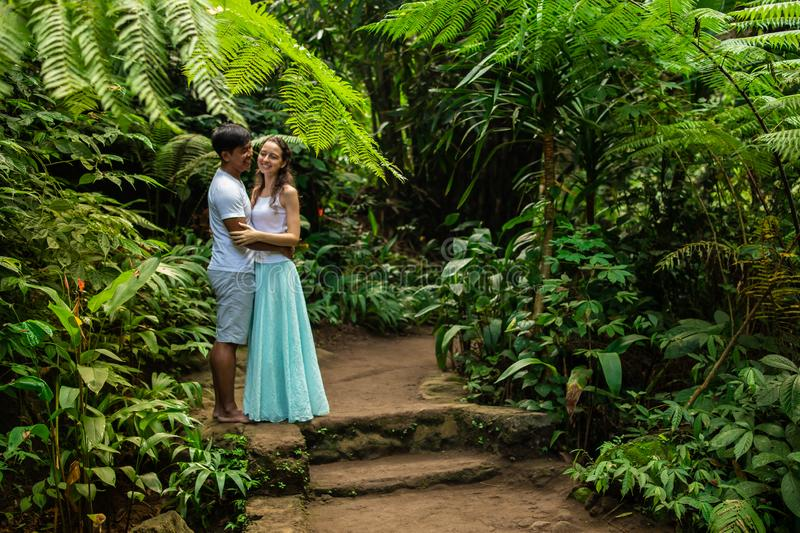 Happy smiling multiracial couple hugging on walking trail in tropical forest. Young mixed race couple on vacation in Asia. Ubud, stock image