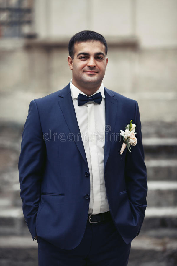 Happy, smiling newlywed groom posing in front of old stairs in a stock images