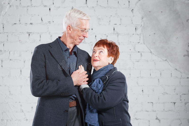 Happy smiling old couple standing cuddling together isolated on white brick background. copy space. royalty free stock images