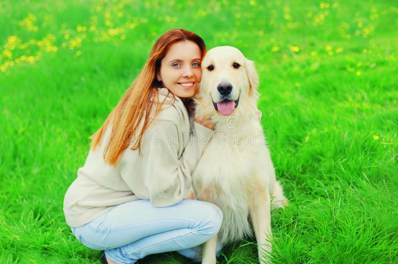 Happy smiling owner and Golden Retriever dog together on grass in summer royalty free stock photos