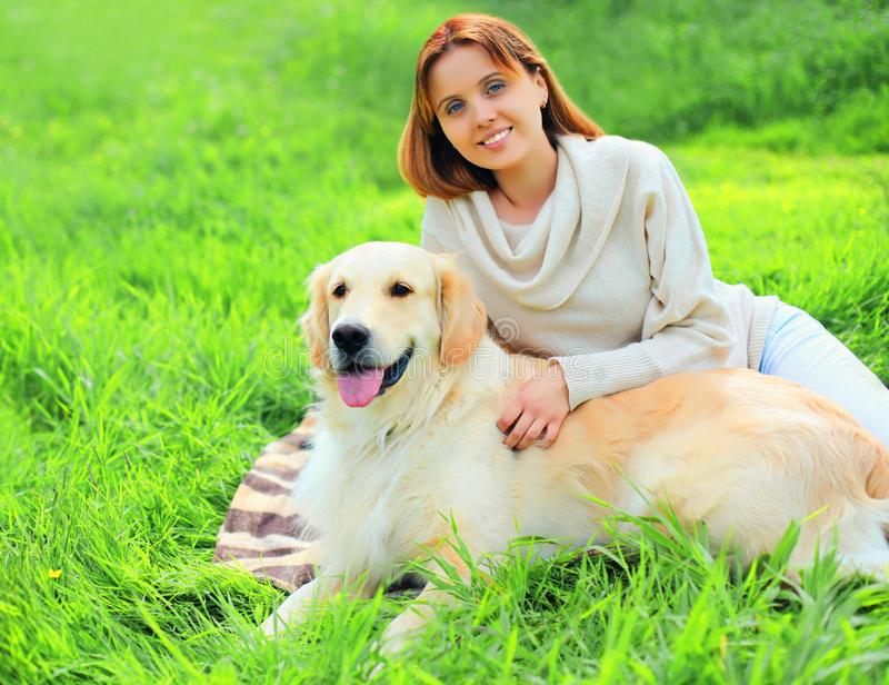 Happy smiling owner and Golden Retriever dog together on grass in summer stock images