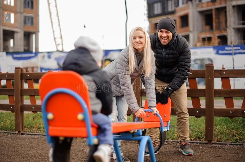 Happy and smiling parents riding on the swing with a little son royalty free stock photos