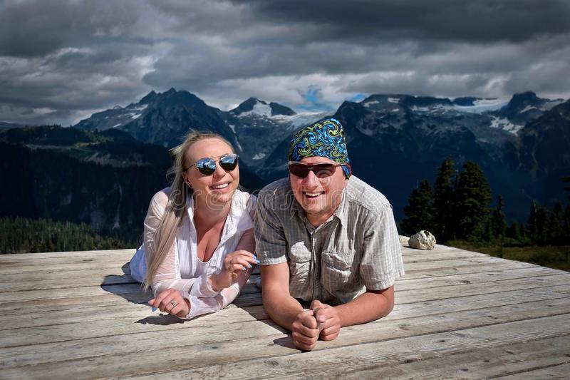 Happy smiling people camping in mountains. Married couple on tent pad having fun and relaxing royalty free stock photography