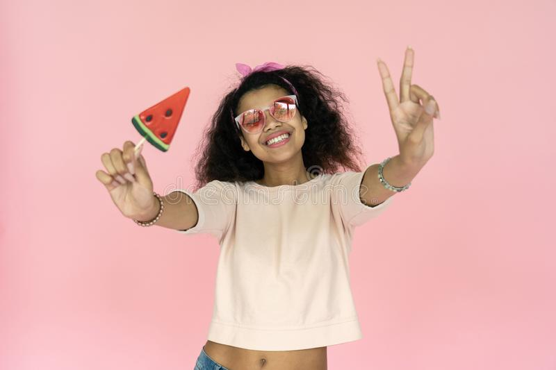 Happy smiling playful young african american teen girl black woman wear stylish glasses eyewear hold watermelon candy ice cream stock photos