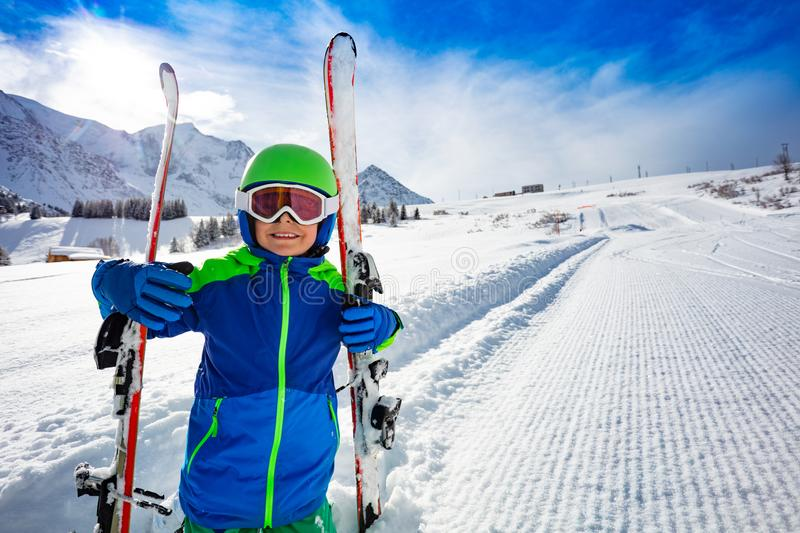 Happy smiling portrait of a boy with ski on slope. Portrait of a boy hold pair of ski and wear helmet with mask smiling over new fresh snow slope piste path in royalty free stock photo