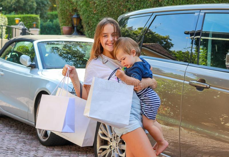 Happy smiling preteen girl with shopping bags holding her little brother coming back after shopping by car. stock images