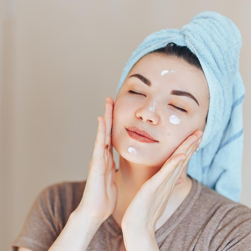 Happy smiling pretty beautiful woman girl with towel on head smiling touch healthy clean soft moisturized hydrated skin care after stock photography