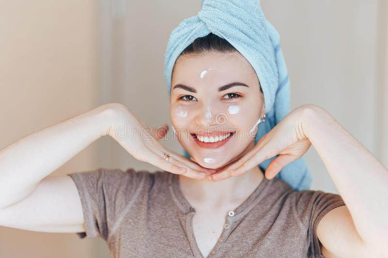 Happy smiling pretty beautiful woman girl with towel on head smiling touch healthy clean soft moisturized hydrated skin care after royalty free stock image