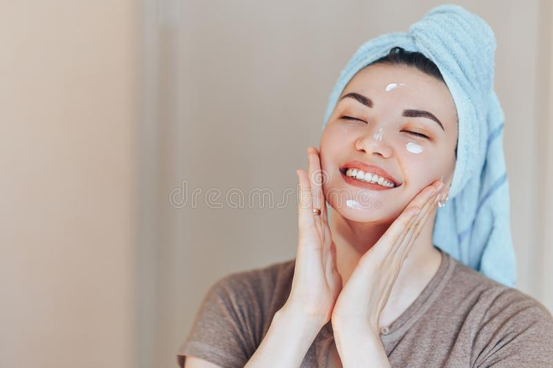 Happy smiling pretty beautiful woman girl with towel on head smiling touch healthy clean soft moisturized hydrated skin care after royalty free stock photography
