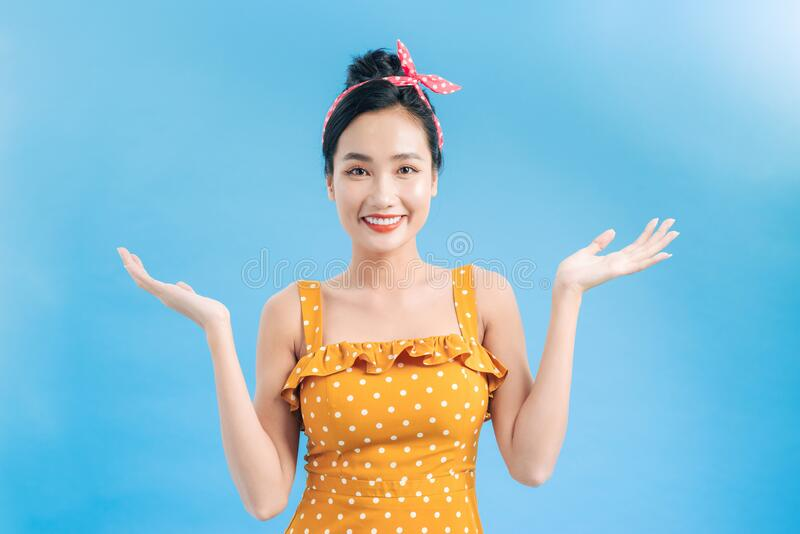 Happy smiling pretty pin up girl wearing hairband bow with empty hands for copy space royalty free stock photo