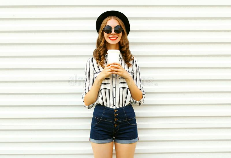 Happy smiling pretty woman with coffee cup in black round hat, shorts, white striped shirt on white wall. Background stock photography
