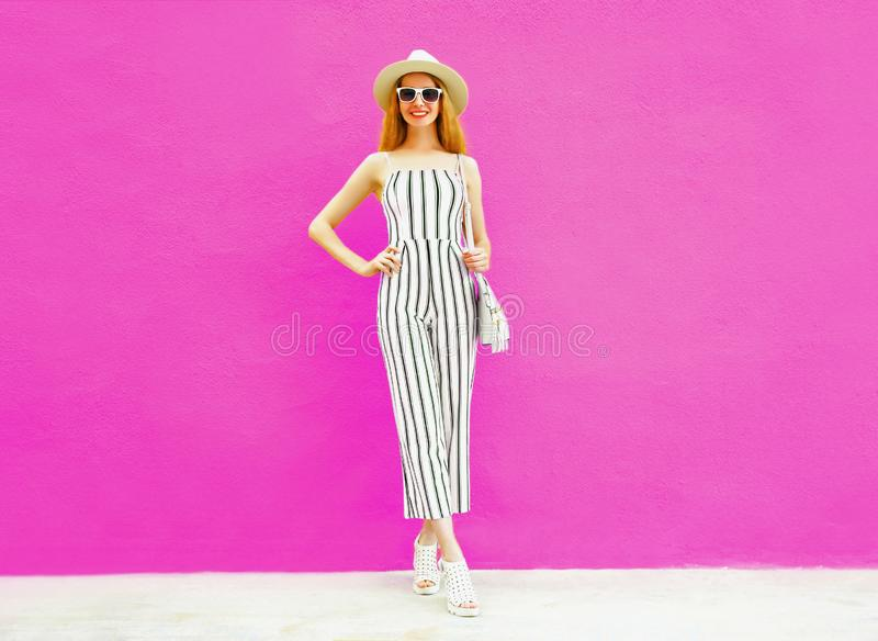 Happy smiling pretty woman in summer round straw hat, white striped jumpsuit on colorful pink wall. Background stock images