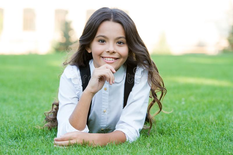 Happy smiling pupil. Girl cute kid laying green grass. Happy kid relaxing outdoors. Girl school uniform enjoy relax stock photos