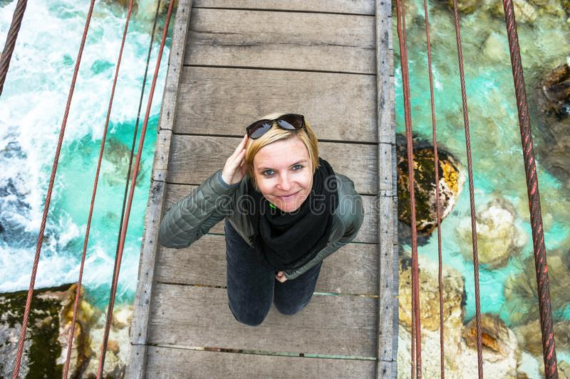 Happy smiling and relaxing woman on an day trip standing on a old wooden hanging bridge royalty free stock photo