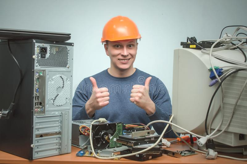 Computer repairman. Computer technician engineer. Support service. Happy smiling repairman in hard hat is repairing the computer and is showing a thumbs up stock image