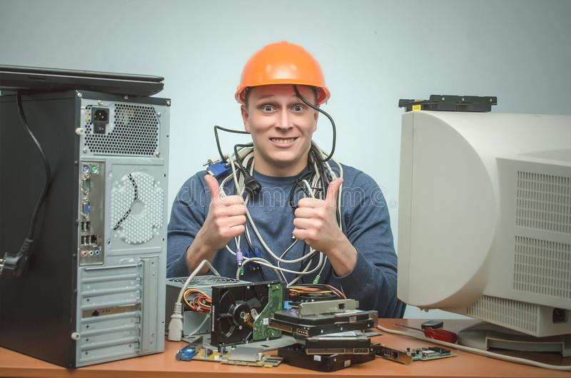 Computer repairman. Computer technician engineer. Support service. Happy smiling repairman in hard hat is repairing the computer and is showing a thumbs up royalty free stock image