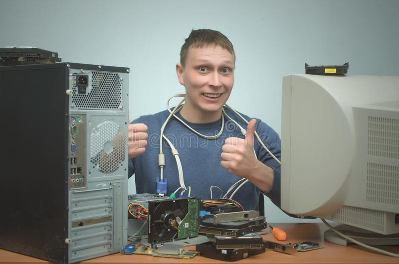 Computer repairman. Computer technician engineer. Support service. Happy smiling repairman is repairing the computer and is showing a thumbs up. Computer royalty free stock photo