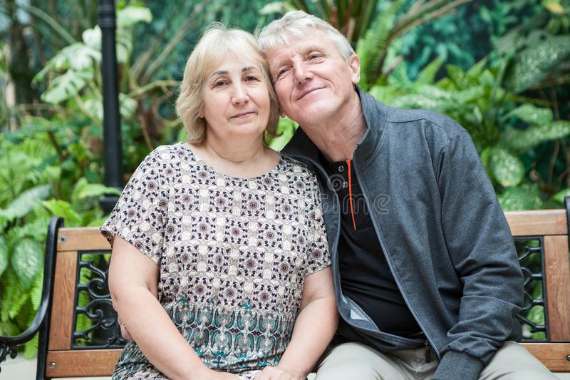 Happy and smiling retired husband and wife portrait, sitting on bench cheek to cheek together stock photography