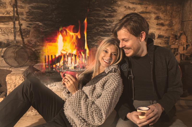 Happy smiling romantic couple relaxing. Happy smiling romantic couple, relaxing over cups of coffee sitting leaning close together on the floor of a rustic stone royalty free stock photo