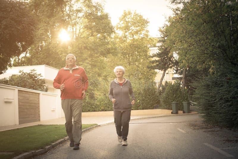 Smiling senior couple jogging in city park. stock photo