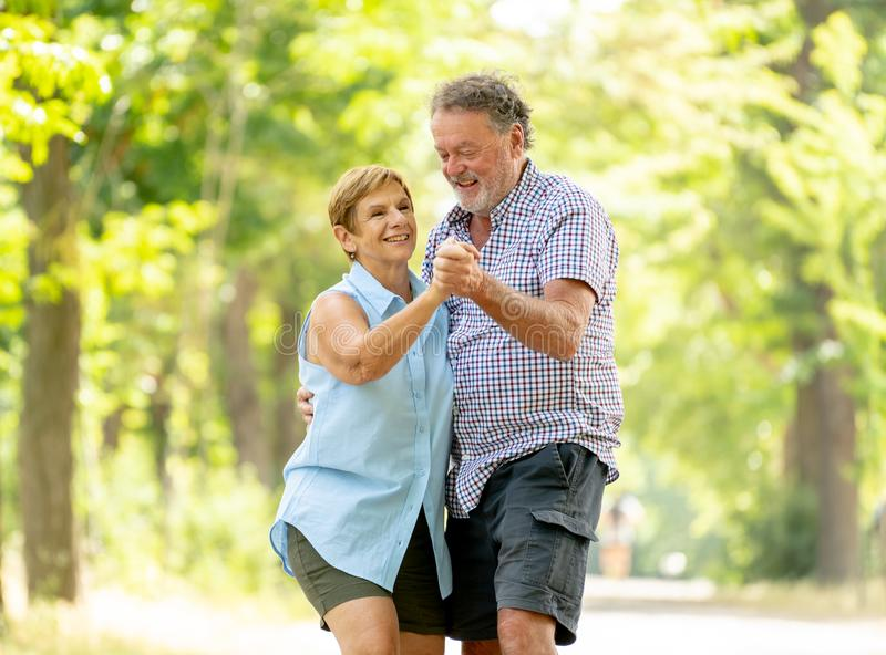 Portrait of a beautiful happy senior couple in love dancing in the park royalty free stock photography