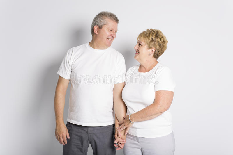Happy smiling senior couple standing together on white background royalty free stock photo