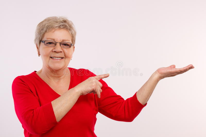 Happy smiling senior female showing empty hand, copy space for text stock image