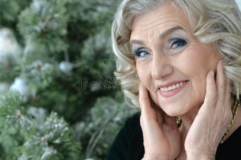 Close up portrait of happy smiling senior woman posing by Christmas tree royalty free stock photos