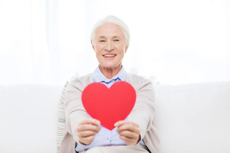 Happy smiling senior woman with red heart at home stock photography