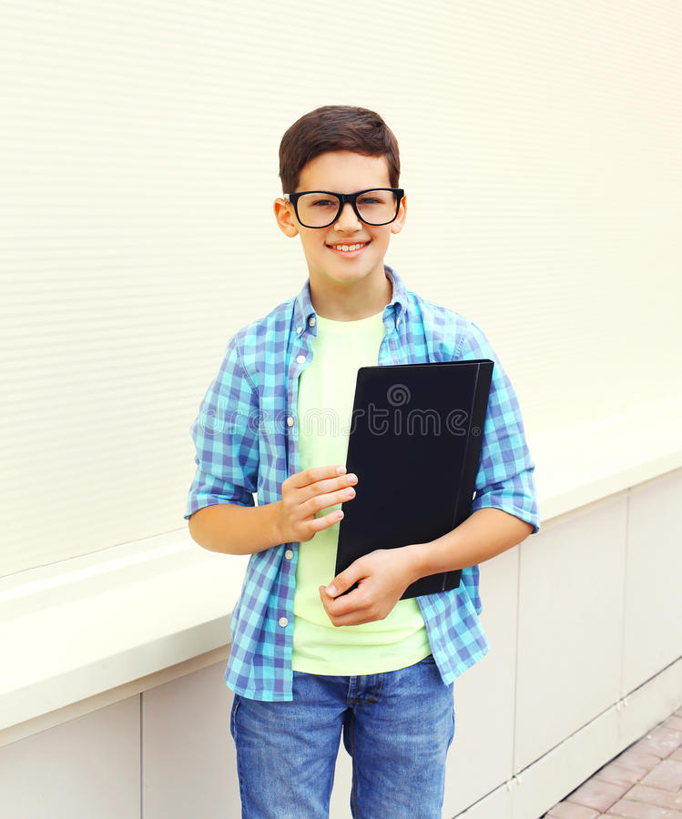 Happy smiling smart teenager boy in glasses with folder or book. Over white background royalty free stock photo