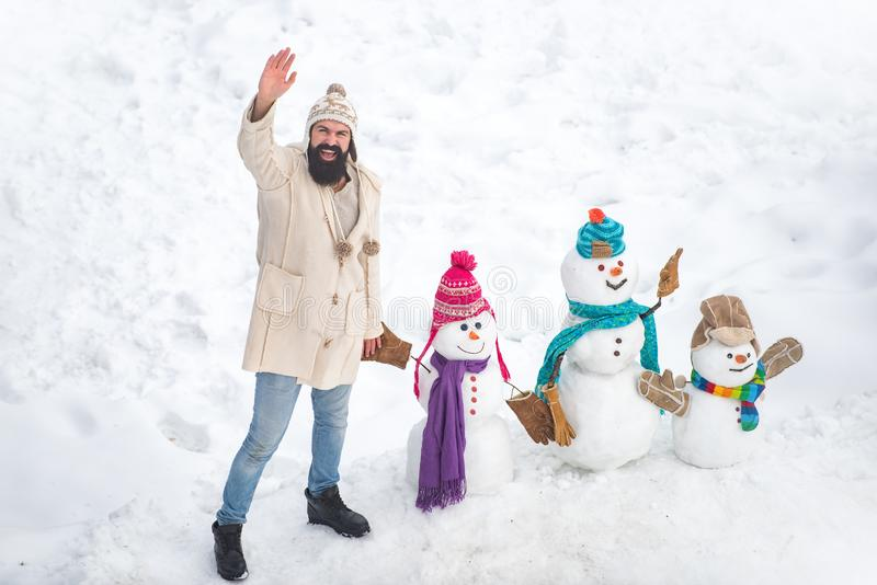 Happy smiling sno man on sunny winter day with Happy father. Father making family of snow man for child. Dad wishes royalty free stock photo
