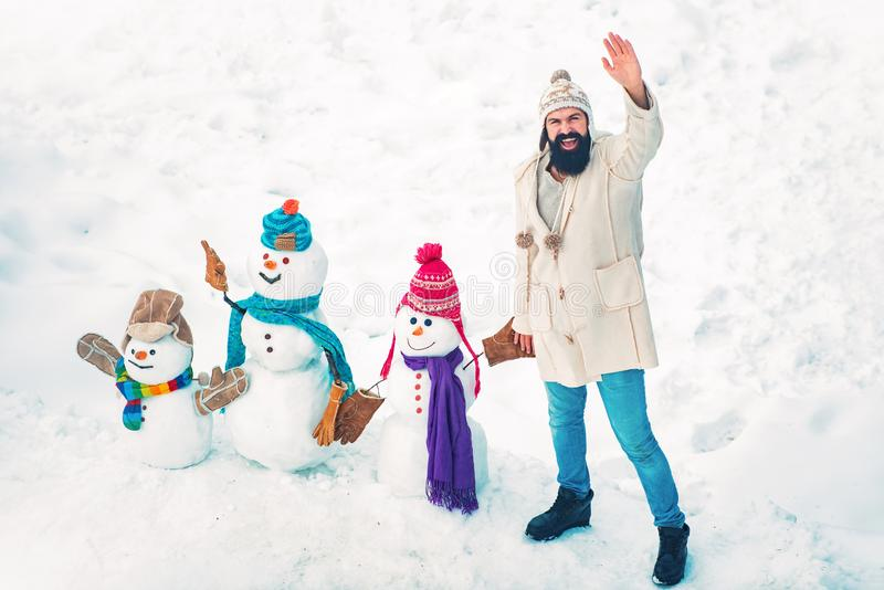 Happy smiling sno man on sunny winter day with Happy father. Father making family of snow man for child. Dad wishes stock photos