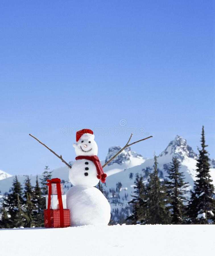 Happy, smiling snowman with Santa hat, Christmas gifts and snowy mountains in background stock photo