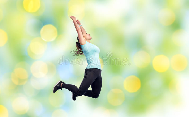 Happy smiling sporty young woman jumping in air. Sport, fitness, motion and people concept - happy smiling young woman jumping in air or dancing over summer stock photography