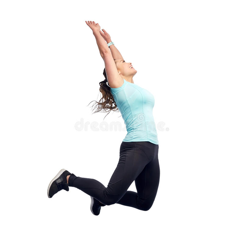 Happy smiling sporty young woman jumping in air. Sport, fitness, motion and people concept - happy smiling young woman jumping in air or dancing over white stock image